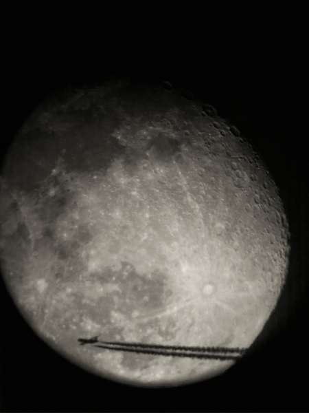 Plane crossing in from of the Moon